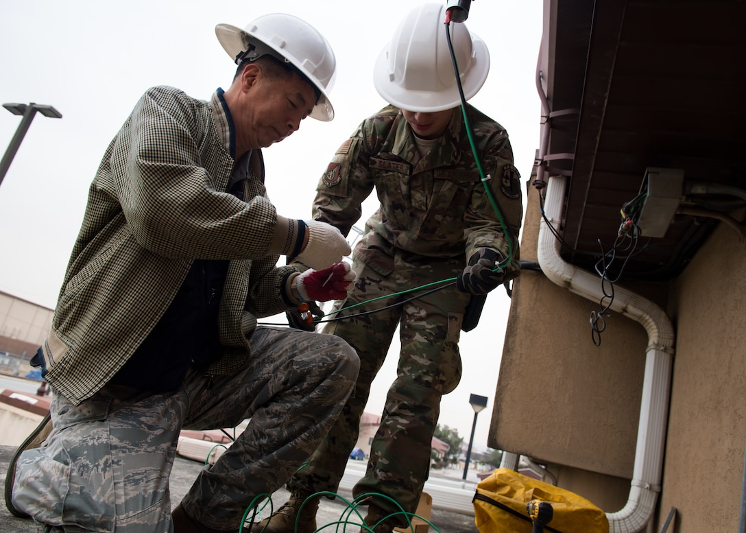 Yong Ui Song, left, and U.S. Air Force Airman 1st Class Jesse Slater, fire alarm technicians with the 51st Civil Engineer Squadron, install a new AS1 antenna on Osan Air Base, Republic of Korea, Nov. 29, 2018.