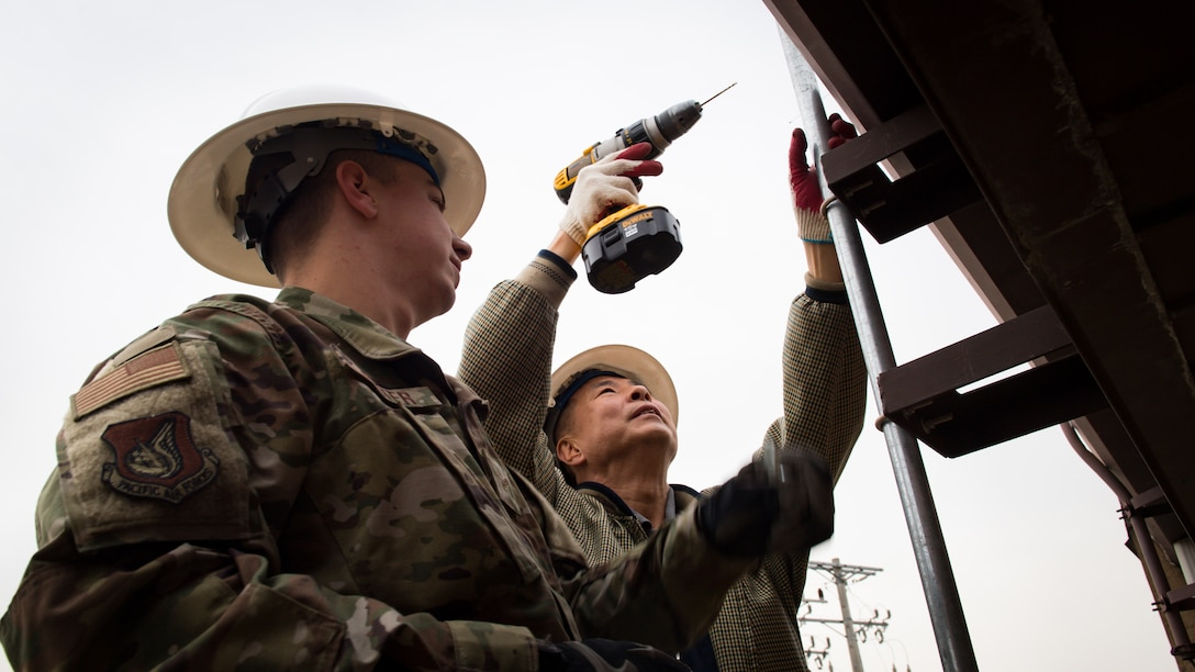 U.S. Air Force Airman 1st Class Jesse Slater, left, and Yong Ui Song, fire alarm technicians with the 51st Civil Engineer Squadron, drill holes into the side of a metal rooftop to secure a new antenna on Osan Air Base, Republic of Korea, Nov. 29, 2018.