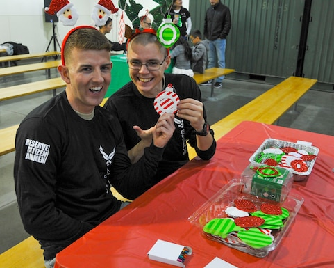 Brandon Unruh and Christopher Eaton, members of the 446th  Development and Training Flight, display their holiday cheer as volunteers for the ornament decorating station at the 446th Airlift Wing's Annual Children's Holiday Party on Joint Base Lewis-McChord, Dec. 2, 2018. The 446th Airlift Wing hosts an annual holiday party to support airmen and their families during the special season.  (U.S. Air Force photo by Staff Sgt.  Mary A. Andom)