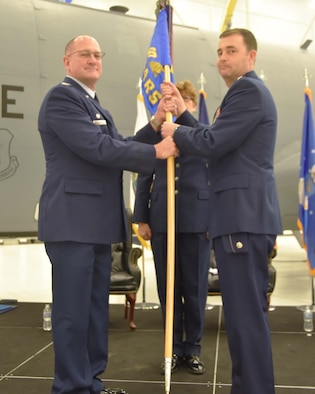 Col. Kevin Rainey, 931st Operations Group commander, gives the guidon to Lt. Col. Stacy Moore, incoming 18th Air Refueling Squadron commander, during a change of command ceremony Dec. 1, 2018, McConnell Air Force Base, Kan.  Prior to this assignment, Moore served as the 931st Operations Support Squadron commander.