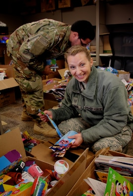 Making her holiday list and checking it twice, Tech Sgt. Teresa Rusnak, picks up the Airman and Family Readiness office's free toy donations for her children.  She is the readiness planner for 932nd Airlift Wing's Inspector General of Inspections at the Illinois unit.  A variety of toys, cookies, and candy are ready to be distributed through the 932nd Airlift Wing Family Readiness Office, led by Deb Teague.  She and other reservists offloaded many parcels of food, toys and cookies recently, on behalf of the Air Force Reserve Command unit located at Scott Air Force Base, Ill. The items will be given out to reservists in Illinois during the December unit training assembly weekend.  (U.S. Air Force photo by Lt. Col. Stan Paregien)