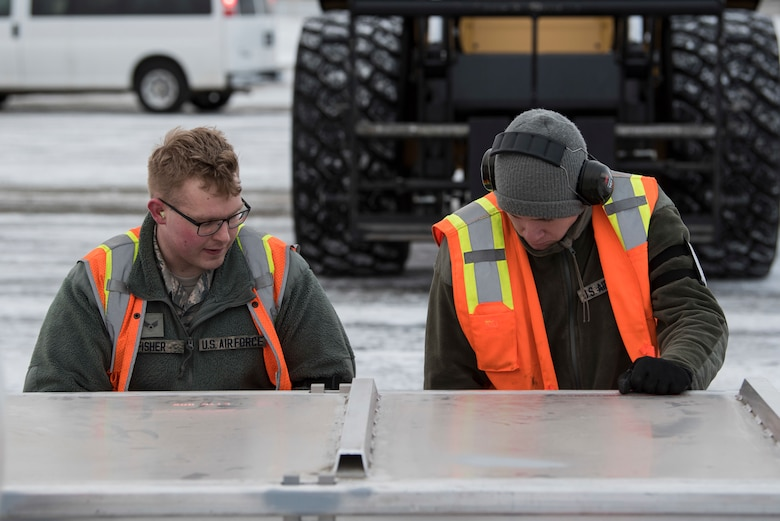 U.S. Air Force Airmen with the 732nd Aircraft Mobility Squadron secure cargo onto a pallet at Joint Base Elmendorf-Richardson, Alaska, Dec. 1, 2018. JBER mission operations continue following a 7.0 earthquake hit to Anchorage, Alaska, on Nov. 30.