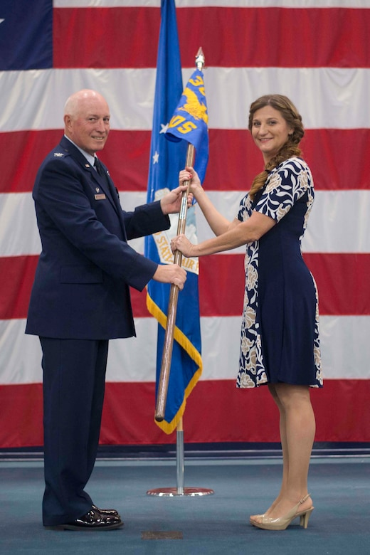 Dr. Tess VanHoy, 307th Medical Squadron honorary commander, accepts the unit guidon from Col. Louis Fehl, 307th MDS commander, during an induction ceremony at Barksdale Air Force Base, Louisiana, Dec. 1, 2018.  VanHoy, serves as a medical doctor in the Shreveport and is the first honorary commander of the 307th MDS. (U.S. Air Force photo by Master Sgt. Ted Daigle)