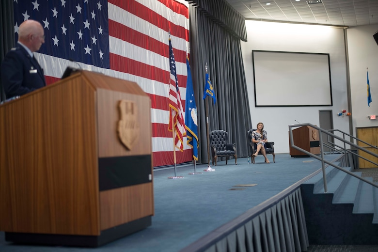Dr. Tess VanHoy, 307th Medical Squadron honorary commander, looks on as Col. Louis Fehl, 307th MDS commander, speaks during an induction ceremony at Barksdale Air Force Base, Louisiana, Dec. 1, 2018.  VanHoy became the first honorary commander of the unit during the induction ceremony.  She is a medical doctor with several years of experience and is the spouse of Col. Rober VanHoy, 307th Bomb Wing commander. (U.S. Air Force photo by Master Sgt. Ted Daigle)
