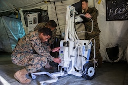 U.S. Navy corpsmen prepare the RadPRO X-ray machine during the capabilities display Nov. 27, 2018 at Camp Foster, Okinawa, Japan. The RadPRO is a portable machine that allows medical staff to conduct X-rays on injured service members after suffering injuries in the field. Sailors with 3rd Medical Battalion, 3rd Marine Logistics Group, established a Role II capabilities display to give service members the opportunity to view their deployable field facilities and employment. Role II facilities give Sailors the ability to offer ultrasound, X-ray, surgery and dental while providing a place for injured service members to be treated. (U.S. Marine Corps photo by Lance Cpl. Mark Fike)