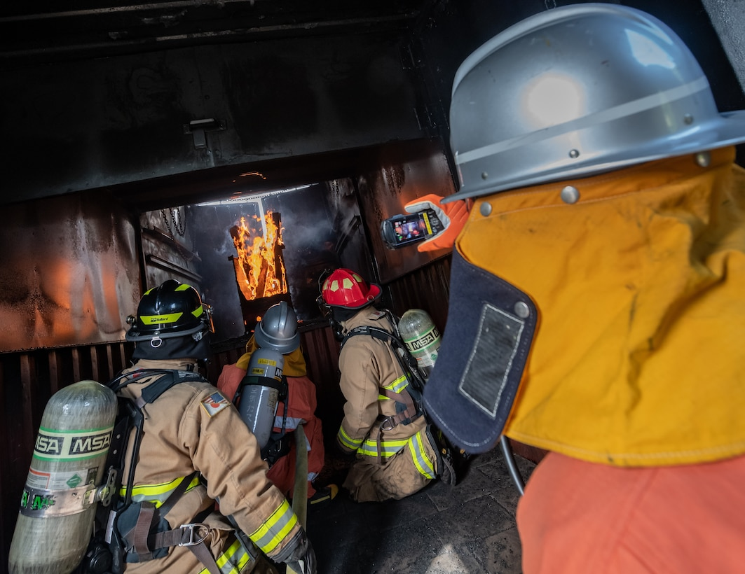 A Japan Air Self Defense Force firefighter from 9th Wing, Naha Air Base, Japan, records video of U.S. Air Force firefighters from the 18th Civil Engineer Squadron and a JASDF firefighter battling a fire during structural live fire training Nov. 15, 2018, at Kadena Air Base, Japan. Before extinguishing the fire, the bilateral teams took time to observe the fire and practice different firefighting techniques. (U.S. Air Force photo by Staff Sgt. Micaiah Anthony)
