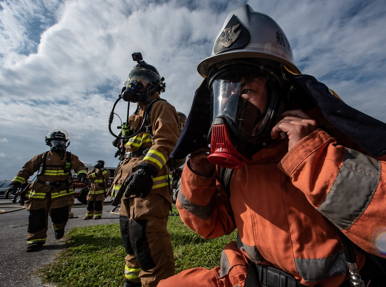 A Japan Air Self Defense Force firefighter from the 9th Wing, Naha Air Base, Japan, dons firefighting equipment Nov. 15, 2018, at Kadena Air Base, Japan. Firefighters conduct training regularly to maintain constant readiness for emergencies. (U.S. Air Force photo by Staff Sgt. Micaiah Anthony)