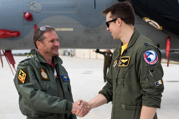 A pilot assigned to the 493rd Fighter Squadron, and a Belgian pilot shake hands while at media event during the NATO Tactical Leadership Programme 18-4 at Amendola Air Base, Italy, Nov. 30, 2018. This event marks the first time the course has been held in Italy, from its normal host location at Albacete Air Base, Spain. (U.S. Air Force photo/ Senior Airman Malcolm Mayfield)