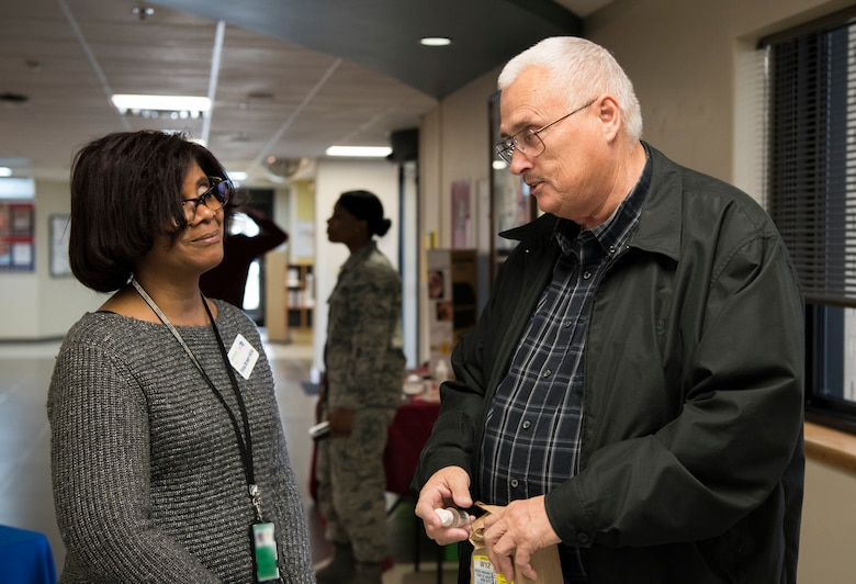 Trina Brown-Hicks, Humana health systems manager, speaks with Phillip R. Wright, attendee, during the 436th Medical Group Health Fair on Nov. 27, 2018, at Dover Air Force Base, Del. Attendees were offered free medical information on topics such as diabetes, disease management, dental health and cervical cancer. (U.S. Air Force photo by Airman 1st Class Zoe M. Wockenfuss) (This image has been obscured to protect personal identification information)