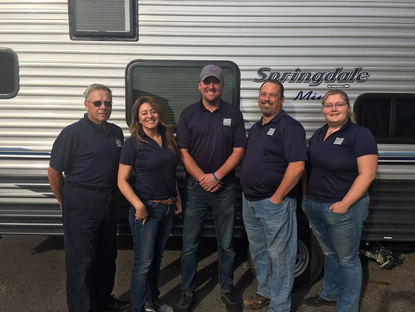 Members of the Outdoor Recreation Team stand in front of a rentable trailer.