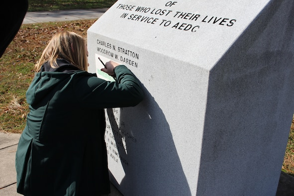 Julie Gesell, granddaughter of the late Wilmer Adam Anderson, an AEDC concrete laborer, sketches the name of her grandfather when visiting the memorial outside the Administration and Engineering Building Nov. 16. Anderson was among four AEDC team members who tragically lost their lives in an accident Dec. 17, 1962, at the J-4 liquid rocket test cell. The memorial is dedicated to all individuals who have lost their lives in service to AEDC. (U.S. Air Force photo by Deidre Ortiz)