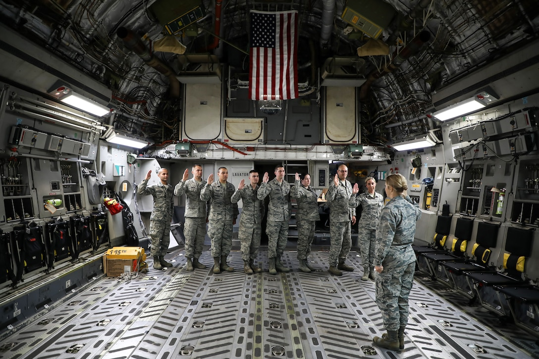 Capt. Beth Shuler, 445th Force Support Squadron, administers the Oath of Enlistment to eight reservists during a re-enlistment ceremony held onboard a 445th Airlift Wing C-17 Globemaster III last month.