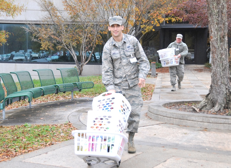 Capt. Jonathon Dias, pictured front, and Master Sgt. Jason Knipe help load baskets of food donated as part of the Thanksgiving Food Basket Program at Arnold Air Force Base. With help from AEDC team members across base, members of the Junior Force Council at Arnold collected donations for 51 food baskets for Coffee County families in need of Thanksgiving meals. (U.S. Air Force photo by Deidre Ortiz)