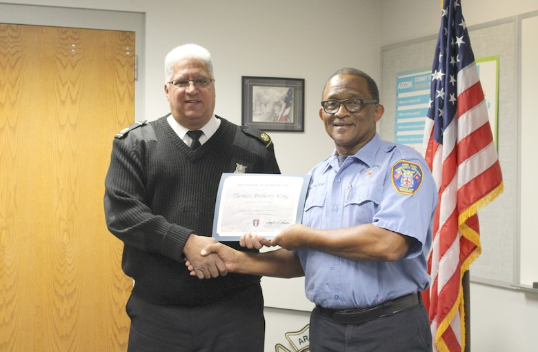 Thomas Anthony King, right, firefighter for Arnold Air Force Base Fire and Emergency Services, receives a certificate recognizing his 25 years of service from Daryle Lopes, chief of Arnold Fire and Emergency Services. (U.S. Air Force photo by Deidre Ortiz)