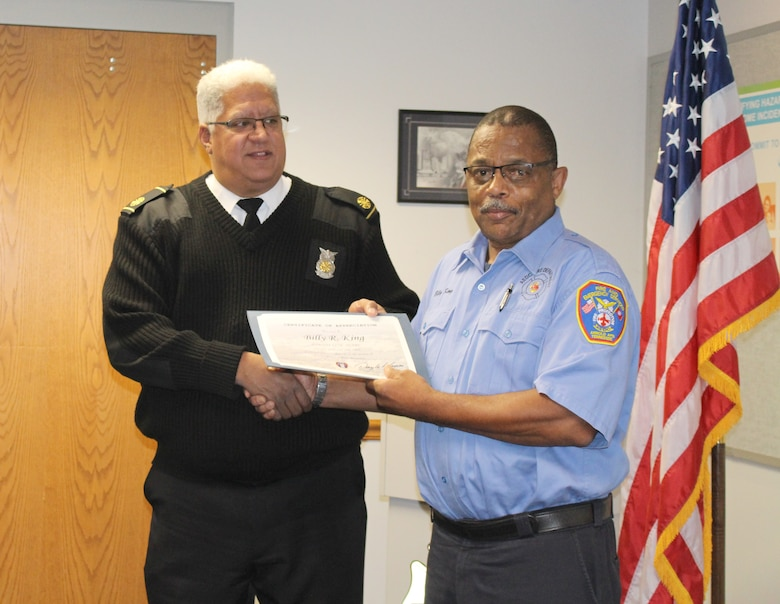 Billy King, right, firefighter for Arnold Air Force Base Fire and Emergency Services, receives a certificate recognizing his 25 years of service from Daryle Lopes, chief of Arnold Fire and Emergency Services. (U.S. Air Force photo by Deidre Ortiz)