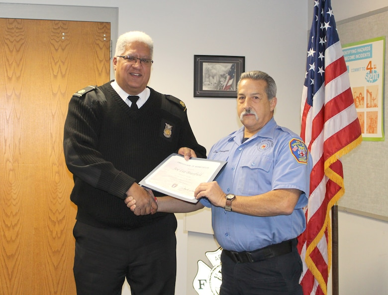 Joe Lee Brassfield, right, driver/operator for Arnold Air Force Base Fire and Emergency Services, receives a certificate recognizing his 20 years of service from Daryle Lopes, chief of Arnold Fire and Emergency Services. (U.S. Air Force photo by Deidre Ortiz)