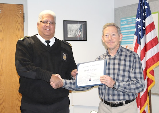 Daryle Lopes, left, chief of Arnold Fire and Emergency Services, receives a certificate recognizing his 15 years of service from Eugene Mittuch, project manager of the Facility Support Services contract at Arnold Air Force Base. (U.S. Air Force photo by Deidre Ortiz)