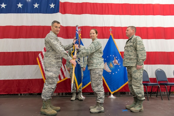 Col. Erik Peterson, the commander of the 115th Fighter Wing, presents the guidon to Lt. Col. Wilhelmina Panzer, the new commander of the 115th Maintenance Group, during the 115 MXG change of command ceremony Dec. 2, 2018, at the 115th Fighter Wing, Truax Field, Wisconsin. Lt. Col. Panzer was previously the inspector general at the 115th Fighter Wing before taking command of the maintenance group.  (U.S. Air National Guard photo by Airman 1st Class Cameron Lewis)