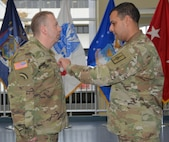 Col. John Andonie, chief of staff for the New York Army National Guard, pins Chief Warrant Officer 3 Albert Thiem, electronic warfare officer for the 42nd Infantry Division,during his promotion ceremony at the Division of Military and Naval Affairs Headquarters in Latham, N.Y., Nov. 9, 2018.