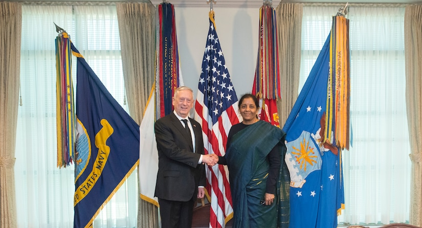 U.S. defense secretary shakes hands with Indian minister of defense.