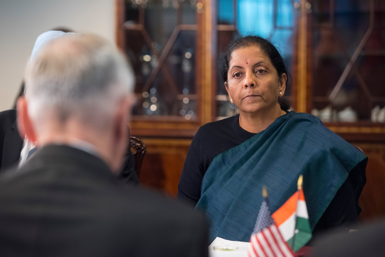 U.S. defense secretary sits at table with Indian minister of defense.