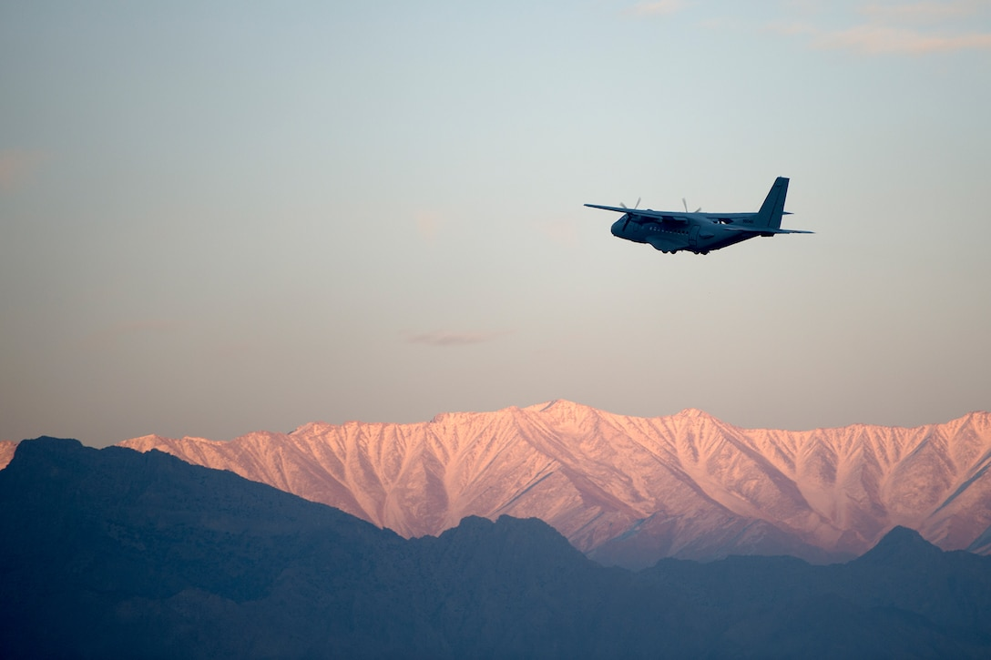 An Air Force aircraft ascends and carries a rescue squadron above the mountains of Afghanistan to perform jump training.