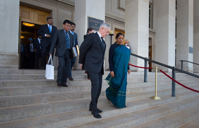 Defense Secretary James N. Mattis walks down steps of the Pentagon steps with Indian Defense Minister Nirmala Sitharaman.