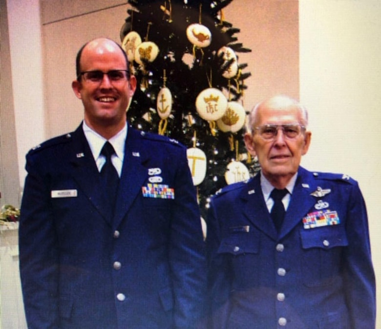 The late retired Col. Delbert L. Mueller and now Maj. David L. Mueller, 374th Aircraft Maintenance Squadron commander, pose for a photo at a holiday event.