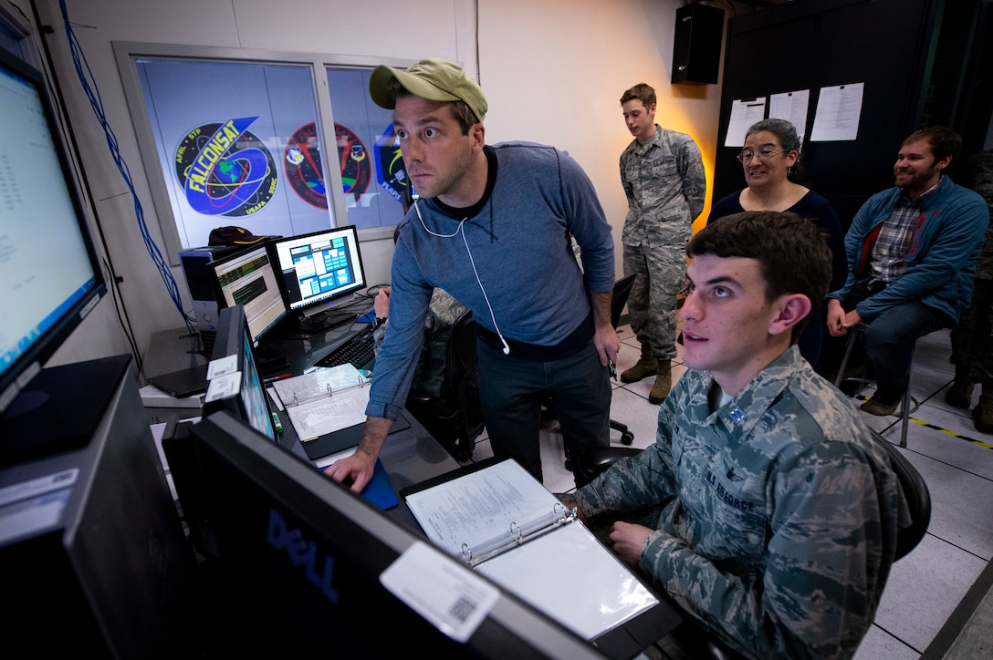 Air Force Academy cadets and civilians look at a computer console.