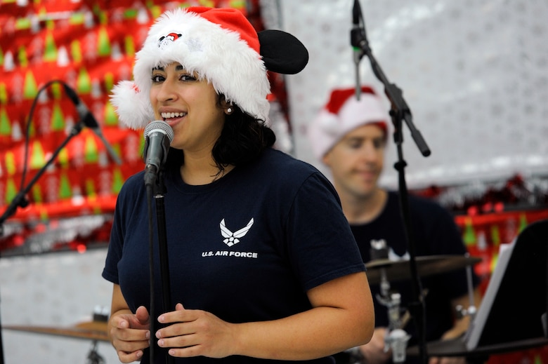 U.S. Air Force Senior Airman Alycia Cancel, U.S. Air Forces Central Command Band vocalist, sings a holiday song during a holiday kick-off event Dec. 1, 2018, at Al Udeid Air Base, Qatar. Service members and their families were able to play holiday games, watch live music performances, interact with Santa Claus and watch a tree lighting ceremony, during the event. (U.S. Air Force photo by Tech. Sgt. Christopher Hubenthal)