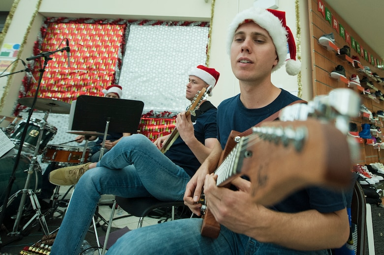 U.S. Air Force Senior Airman Guy James, foreground, U.S. Air Forces Central Command Band guitarist, and Staff Sgt. Bryan Andrews, AFCENT Band bassist, play holiday songs during a holiday kick-off event Dec. 1, 2018, at Al Udeid Air Base, Qatar. Service members and their families were able to play holiday games, watch live music performances, interact with Santa Claus and watch a tree lighting ceremony, during the event. (U.S. Air Force photo by Tech. Sgt. Christopher Hubenthal)