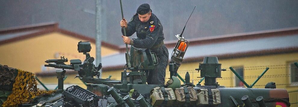 Romania Army CW2 Miron Alexandra installs a radio antenna on a TR-85 tank, Hohenfels, Germany, Dec. 2, 2018