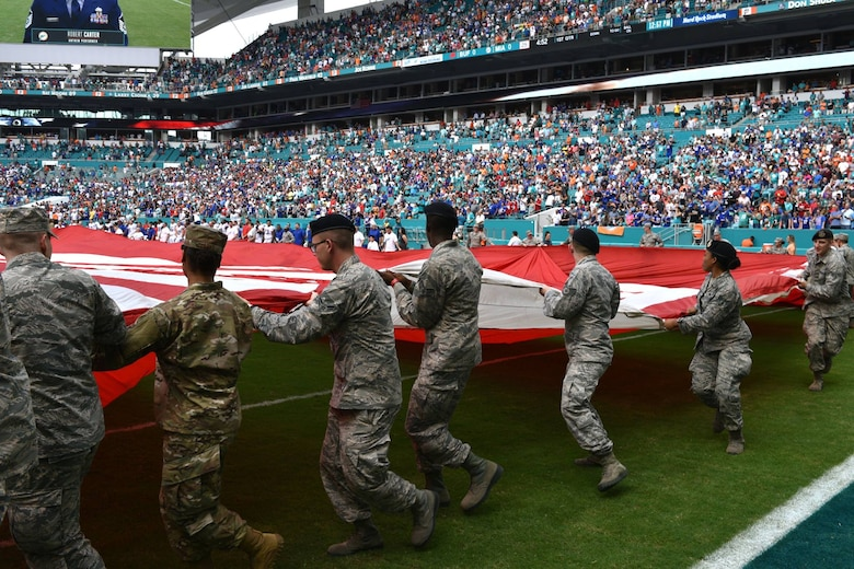 Airmen and local community members unfurl the flag for the National Anthem prior to the start of a Miami Dolphins football game on Dec 2, 2018 in Miami. Approximately 75 Airmen from Patrick Air Force Base, Fla. participated in the event. (U.S. Air Force photo by Airman 1st Class Dalton Williams)