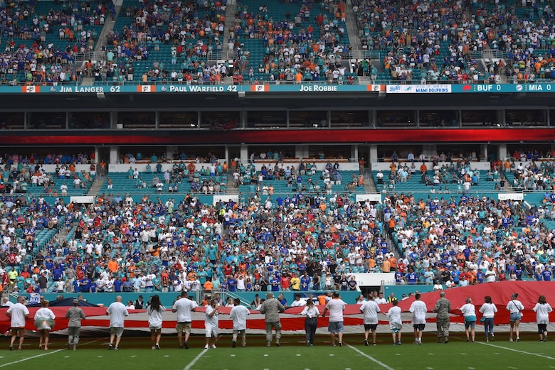 Airmen and local community members unfurl the flag for the National Anthem prior to the start of a Miami Dolphins football game on Dec 2, 2018 in Miami. Approximately 75 Airmen from Patrick Air Force Base, Fla. participated in the event. (U.S. Air Force photo by Tech. Sgt. Andrew Satran)