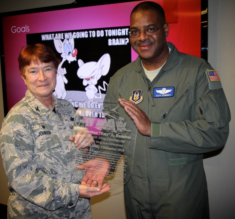 "Commander of the 932nd Maintenance Group, Col. Sharon Johnson, presents a farewell gift to outgoing vice commander, Col. Esty Ramirez during his final staff meeting on Nov. 30, 2018, at Scott Air Force Base, Ill.  Part of the inscription reads, ""The 932nd Airlift Wing has been remarkably blessed to have you as leader, mentor and friend.  You have the unique ability to connect with people and your servant leadership embodies the Air Force core values.""  (U.S. Air Force photo by Lt. Col. Stan Paregien)"