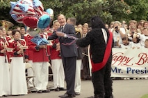 President Bush is accosted by a gorilla carrying mylar balloons in celebration of the President's 65th birthday, South Lawn of the White House, 12 Jun 89.