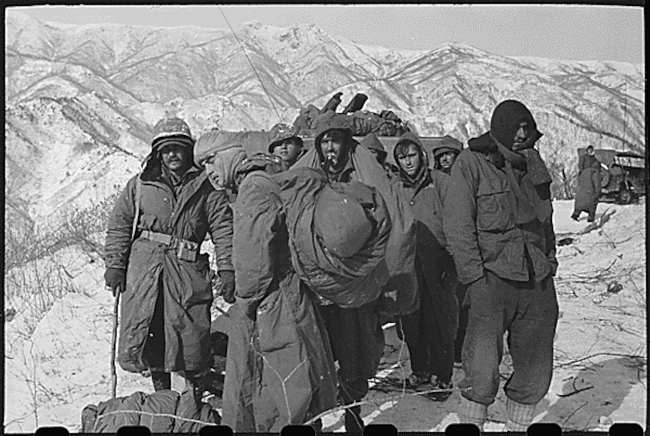 A black and white photo of Marines standing in the snow.