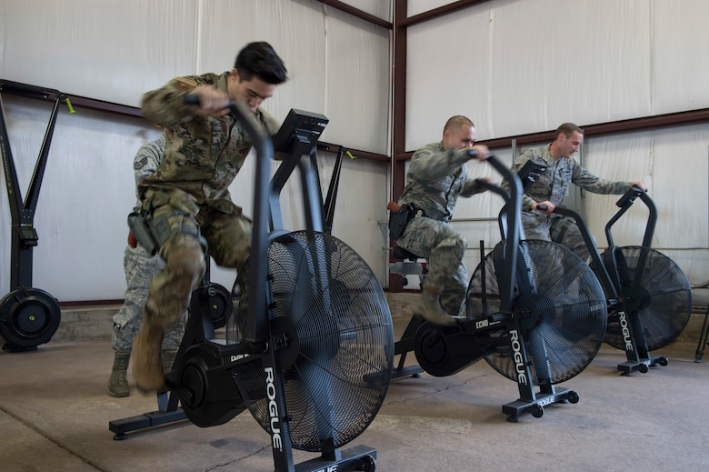 Members of 97th Security Forces Squadron staff support team use exercise bikes