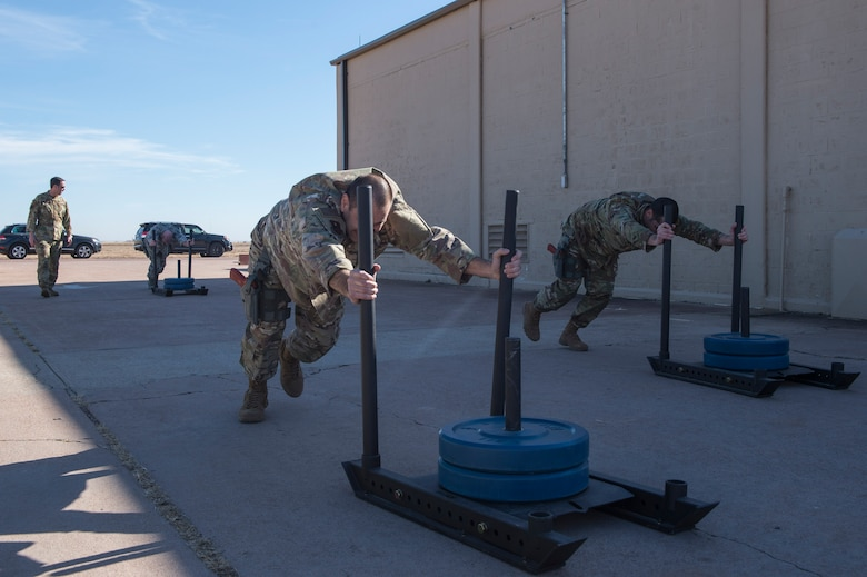 Members of the 97th Force Support Squadron team push weighted sleds