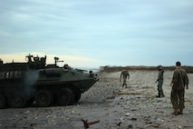 A U.S. Marine guides a light armored vehicle with the 2nd Light Armored Reconnaissance Battalion onto Onslow Beach at Camp Lejeune, North Carolina, Nov. 30, 2018. Marines and Sailors with the 24th Marine Expeditionary Unit participated in Exercise Trident Juncture in Norway and Iceland and returned home from USS New York (LPD 21). (U.S. Marine Corps photo by Gunnery Sgt. Robert Durham)
