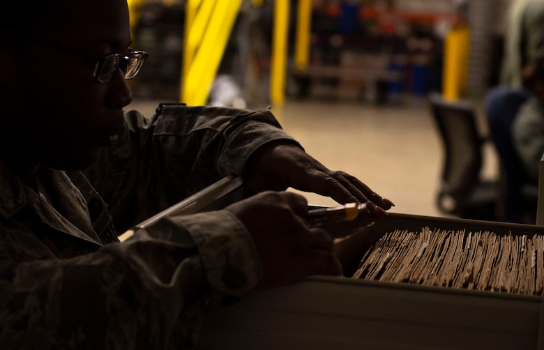 U.S. Air Force Senior Airman Shanice Smith, 20th Logistics Readiness Squadron individual protective equipment journeyman, sorts through customer gear logs at Shaw Air Force Base, S.C., Nov. 30, 2018.