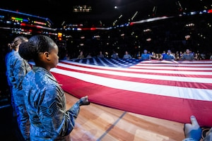 Members of the 59th Medical Wing, Joint Base San Antonio-Lackland, participate in the Living Flag ceremony held before the Dec. 2 game between the San Antonio Spurs and Portland Trailblazers at the AT&T Center in San Antonio, Texas. Nearly 30 Airmen held the flag aloft during the singing of the national anthem.  (Photo courtesy of the San Antonio Spurs)