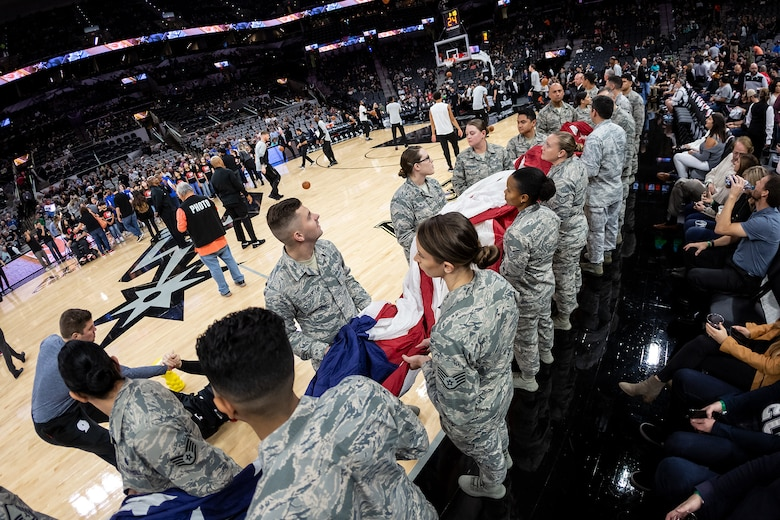 Members of the 59th Medical Wing, Joint Base San Antonio-Lackland, participate in the Living Flag ceremony held before the Dec. 2 game between the San Antonio Spurs and Portland Trailblazers at the AT&T Center in San Antonio, Texas. Nearly 30 Airmen held the flag aloft during the singing of the national anthem. 