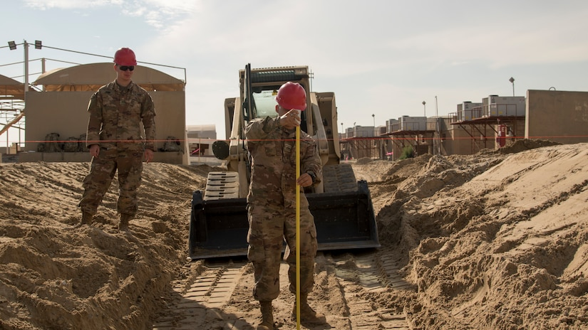 """A U.S. Army Soldier with the 526th Engineer Construction Company, 92nd Engineer Battalion, 28th Engineer Brigade, measures the depth of a trapezoidal ditch being dug at Camp Arifjan, Kuwait, Nov. 28, 2018. U.S. Army Capt. Bryan Thompson, the commander of the 526th ECC, said, """"The one thing I really want to highlight is, I'm really blessed to have such a great team."""" The Soldiers of the 526th ECC conducted constant operations to immediately resolve flooding earlier in the month, and continue to improve drainage features at Camp Arifjan with projects like this ditch."""