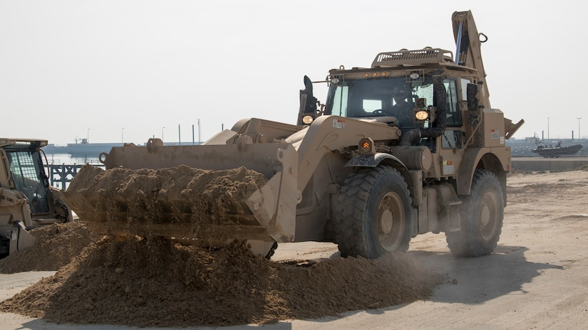 U.S. Army Spc. Daniel Boyet, a heavy equipment operator with Alpha Company, 150th Brigade Engineer Battalion, Mississippi Army National Guard, uses a High Mobility Engineer Excavator to move sand into a position where it can be used to fill in a ditch created by rainwater runoff at the beach at Kuwait Naval Base, Kuwait, Nov. 30, 2018. The hazard created by the ditch made the beach unsafe for training until the 150th BEB was able to fix it with help from Area Support Group-Kuwait's Directorate of Public Works.
