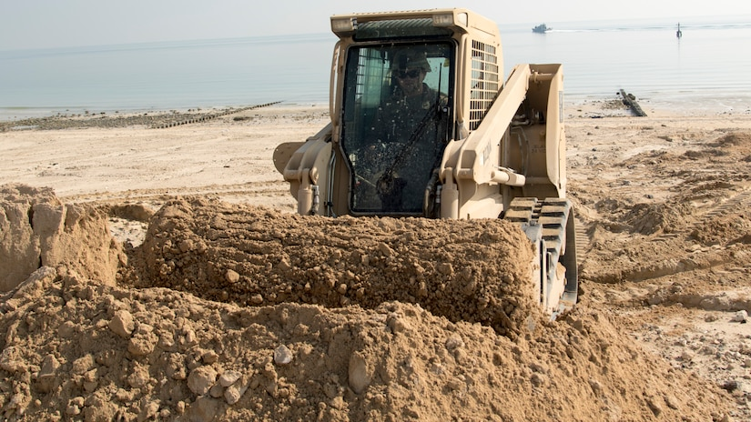 U.S. Army Spc. Laramie Graham, a heavy equipment operator with Bravo Company, 150th Brigade Engineer Battalion, Mississippi Army National Guard, uses a skid-steer to move sand to fill in a ditch formed by rainwater runoff at the beach at Kuwait Naval Base, Kuwait, Nov. 30, 2018. The hazard created by the ditch made the beach unsafe for training until the 150th BEB was able to fix it with help from Area Support Group-Kuwait's Directorate of Public Works.