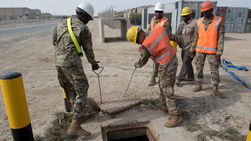 U.S. Army Soldiers from U.S. Army Network Enterprise Center-Kuwait, remove a manhole cover to assess how much water has collected in an access service point at Camp Buehring, Kuwait, Dec. 1, 2018. Keeping communication lines operational during extreme weather events is an essential task to ensure our personnel remain capable to accomplish their mission.