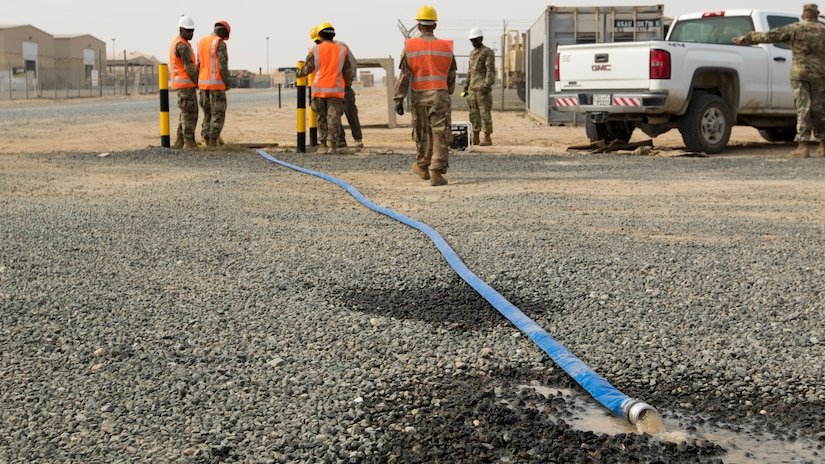 A hose discharges water being pumped from a flooded access service point by a team of Soldiers from U.S. Army Network Enterprise Center-Kuwait, at Camp Buehring, Kuwait, Dec. 1, 2018. Kuwait has experienced unusually heavy rainfall and flooding this past month, and U.S. Army Soldiers have risen to the challenge to remain operational despite the weather challenges.