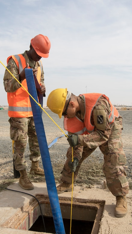 U.S. Army Soldiers Pfc. Dequan McFadden and Sgt. Huascar Hernandez with U.S. Army Network Enterprise Center-Kuwait, lower a pump into a flooded access service point at Camp Buehring, Kuwait, Dec. 1, 2018. Keeping communication lines operational during extreme weather events is an essential task to ensure our personnel remain capable to accomplish their mission.