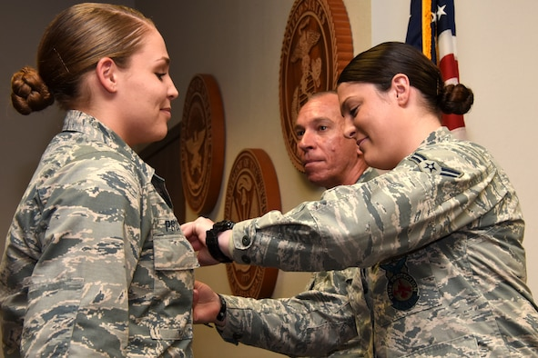 U.S. Air Force Lt. Col. Scott Cline, 312th Training Squadron commander, watches as Airman 1st Class Erin Prosser pins a duty badge onto Airman Emma Prosser at her graduation from the Louis F. Garland Department of Defense Fire Academy on Goodfellow Air Force Base, Texas, Dec. 3, 2018. Erin and Emma Prosser are twins, Erin joined the Air Force shortly before her sister and graduated the fire academy in March of 2018. (U.S. Air Force photo by Airman 1st Class Seraiah Hines/Released